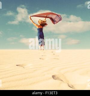 Rear view of a woman holding a scarf that's blowing in the wind - Stock Photo