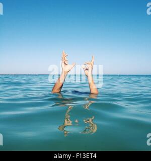 Human hands coming out of the sea - Stock Photo