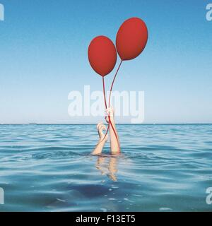 Human hands coming out of the sea holding two balloons - Stock Photo