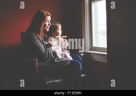 Baby girl sitting on her mother's lap, looking out the window - Stock Photo