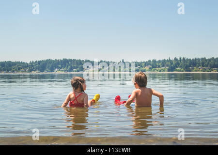 Rear view of a boy and a girl sitting in shallow lake water - Stock Photo
