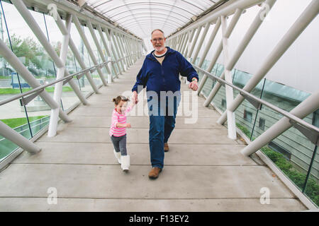 Girl and her grandfather holding hands, walking across a walkway - Stock Photo