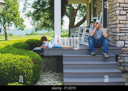 Man sitting on porch steps looking at son - Stock Photo