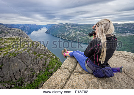 Woman sitting on the edge of pulpit rock taking a photo, Norway - Stock Photo