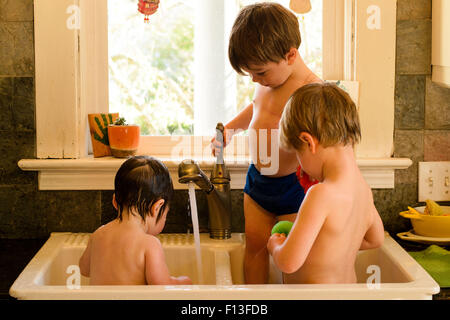 Three children in a butlers sink having a wash - Stock Photo