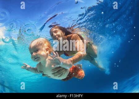 Family lifestyle. Holiday with children. Little funny baby swimming lesson, games with fun at swimming pools with - Stock Photo