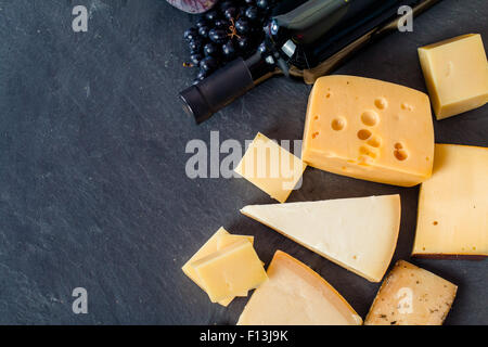 Different types of cheeses, red wine, grapes and figa on black board, top view - Stock Photo