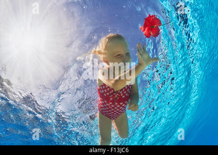 Happy little baby with smile and open eyes diving in swimming pool with clear blue water for a bright red flower. - Stock Photo