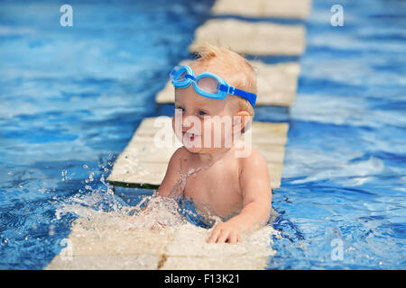 Happy smiling baby with underwater goggles swimming and playing with splashes in the clear blue water in pool. - Stock Photo