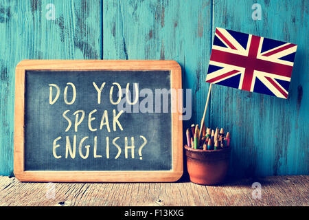 a chalkboard with the text do you speak english? written in it, a pot with pencils and the flag of the United Kingdom, - Stock Photo
