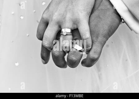 The bride groom proudly showing off their wedding rings after the wedding service - Stock Photo