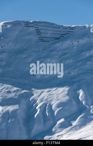 Avalanche barriers high up on a snow covered mountain at Belalp/Blatten, Switzerland (Valais canton). - Stock Photo