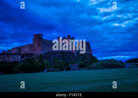 Late evening dusk view of Bamburgh Castle in Northumberland with a very stormy sky and a red hue on the walls of - Stock Photo