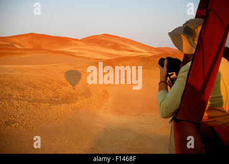 Tourists taking photos from hot air balloon ride over the Namib desert, Namibia, February 2005. - Stock Photo
