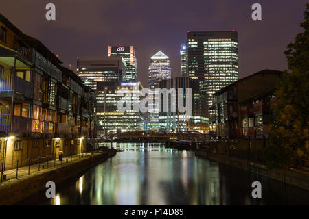 LONDON, UK - 16TH JULY 2015: The outside of Canary Wharf in London at night showing the office buildings and reflections - Stock Photo
