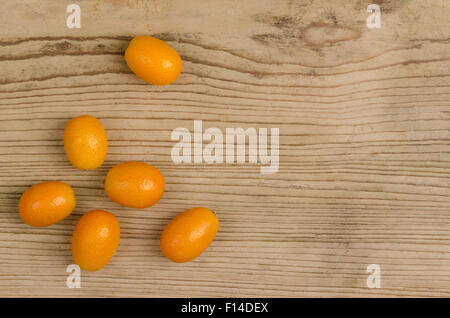 Oval kumquats on old spruce wood board. Closeup. Macro photo from above. - Stock Photo