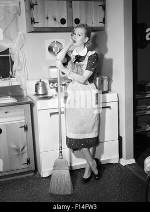 1950s TIRED HOUSEWIFE IN APRON STANDING IN FRONT OF STOVE LEANING ON BROOM LOOKING AT CAMERA - Stock Photo