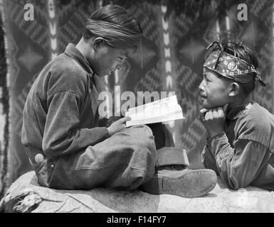 1930s TWO NATIVE AMERICAN NAVAJO BOYS READING BOOK - Stock Photo