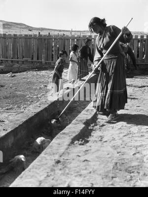 1930s NATIVE AMERICAN WOMEN CHILDREN LEADING SHEEP THROUGH SHEEP DIP AT TUBA CITY ARIZONA NAVAJO INDIAN RESERVATION - Stock Photo