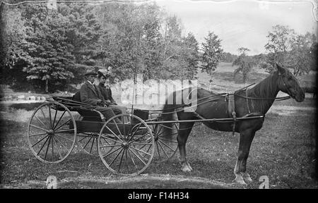 1890 1890s TURN OF THE 20TH CENTURY COUPLE MAN WOMAN RIDING IN HORSE DRAWN BUGGY CARRIAGE LOOKING AT CAMERA - Stock Photo