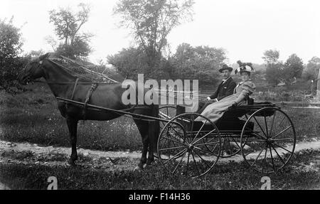 1890s TURN OF THE 20TH CENTURY COUPLE MAN WOMAN RIDING IN HORSE DRAWN BUGGY CARRIAGE LOOKING AT CAMERA - Stock Photo