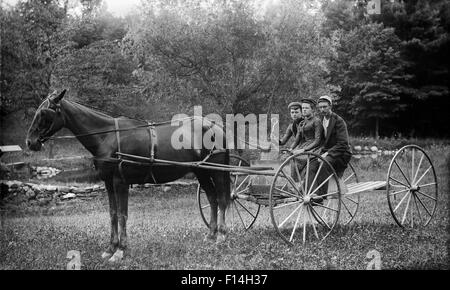 1890s TWO WOMEN ONE MAN RIDING IN HORSE DRAWN BUGGY CARRIAGE LOOKING AT CAMERA - Stock Photo