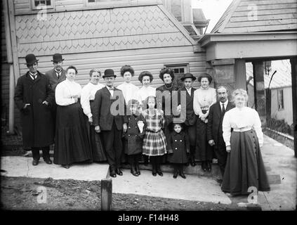 1890 1890s TURN OF 20TH CENTURY GROUP PORTRAIT FAMILY THREE GENERATIONS STANDING POSING BY SIDE OF HOUSE LOOKING - Stock Photo