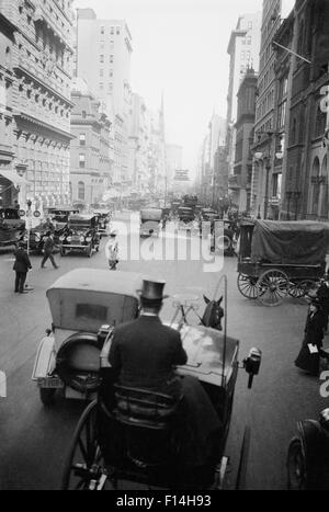 1910s 5TH AVE AT 43rd LOOKING NORTH CARS WAGONS PEDESTRIANS A HANSOM CAB AND DRIVER IN TOP HAT IN FOREGROUND NEW - Stock Photo