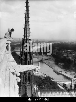 1920s TWO WOMEN LOOKING OUT FROM TOP OF NOTRE DAME CATHEDRAL PARIS FRANCE - Stock Photo
