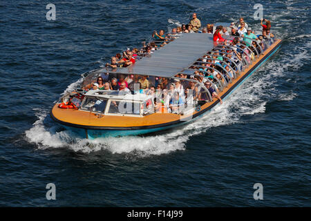 Fully occupied canal cruise boat southbound at full speed at Havnegade just before passing under Knippelsbro Bridge - Stock Photo