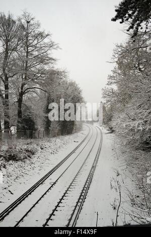 Deserted snow-covered suburban railway line looking towards Caterham, Surrey, England following heavy snowfall - Stock Photo