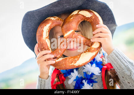 little bavarian girl with a big pretzel. selective focus - Stock Photo