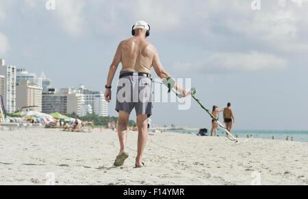 Senior man using metal detector on beach - Stock Photo