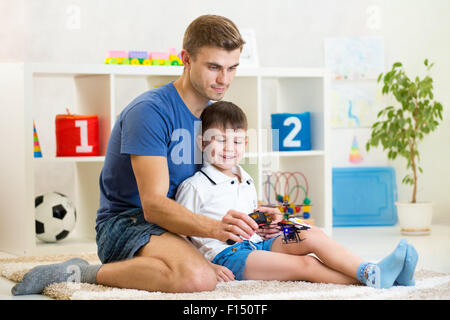 Kid boy holding a radio remote control for helicopter - Stock Photo