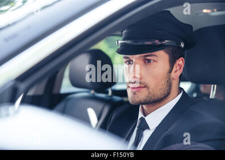 Portrait of a handsome male chauffeur sitting in a car - Stock Photo