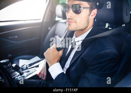 Portrait of a handsome male chauffeur in sunglasses sitting in a car - Stock Photo