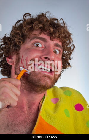 Silly bearded man cuts his face while shaving off his beard - Stock Photo