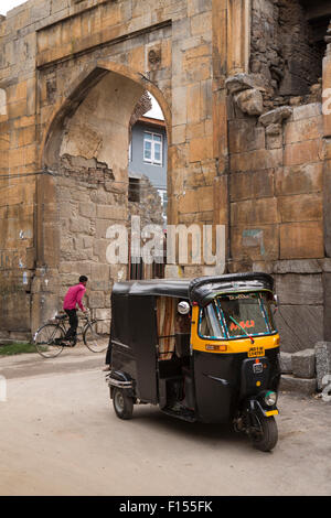 India, Jammu & Kashmir, Srinagar, autorickshaw parked at remains of Mughal arched gate in old city wall - Stock Photo