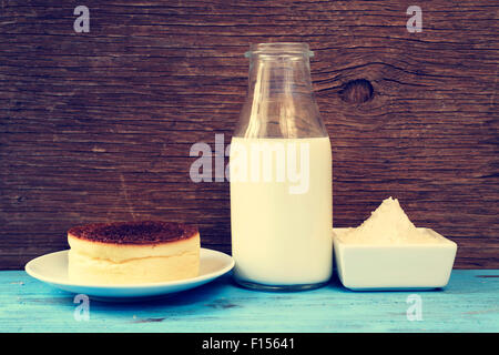 a cheesecake and some of the ingredients to prepare it, such as light cream or wheat flour, on a blue rustic wooden - Stock Photo