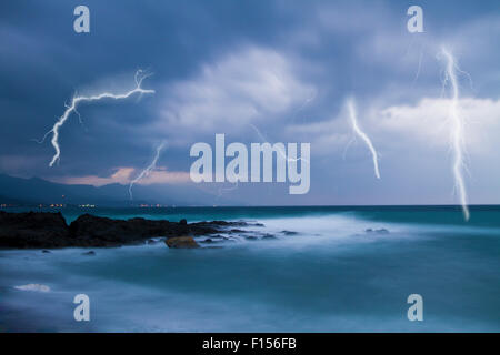 Lightning flashes across the beach from a powerful storm - Stock Photo