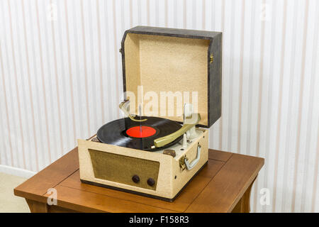 Vintage record player with vinyl album on wood table. - Stock Photo
