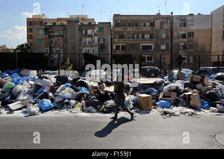 Beirut, Beirut, Lebanon. 27th Aug, 2015. A woman walks past piles of garbage in the Lebanese capital Beirut on August - Stock Photo