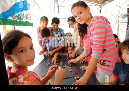 Damascus. 27th Aug, 2015. Syrian children play with plasticene during an extracurricular activity at a makeshift - Stock Photo