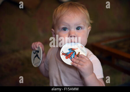 An eleven month old baby chewing on a plastic coaster to alleviate the pain and discomfort of tooth ache. - Stock Photo