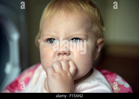 A teething eleven month old baby chewing on her fingers to alleviate the discomfort of tooth ache. - Stock Photo