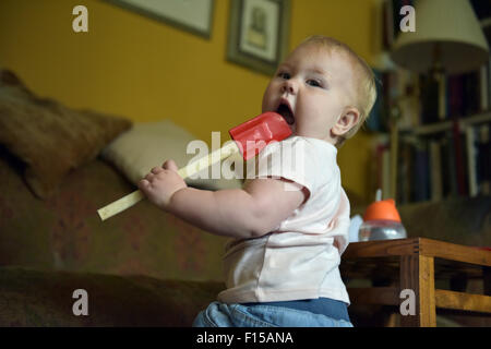 An eleven month old baby chewing on a red plastic kitchen spoon-spatulas to alleviate the pain and discomfort of - Stock Photo