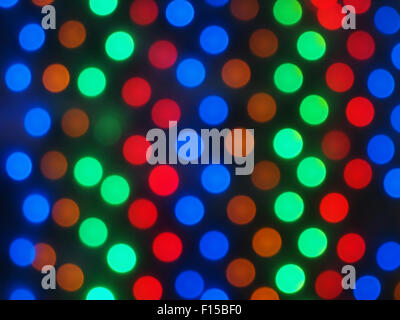 Defocused colored lights fill the entire frame with dark base was blurred for use as a background - Stock Photo