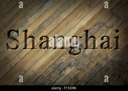 Engraving spelling the city Shanghai on textured old surface - Stock Photo