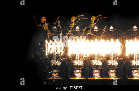 Horrifying vintage Halloween themed skeletons run along lightbulbs - Stock Photo