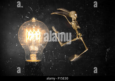 Horrifying vintage Halloween themed skeleton jumping past lightbulb - Stock Photo